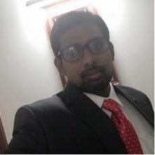selfie picture of a man in suit and wearing spectacles